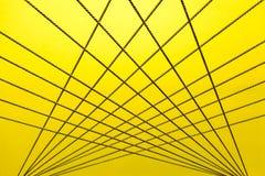 Kruisend kabels creeer een abstract patroon op geel en wit Royalty-vrije Stock Foto's