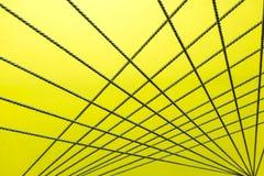 Kruisend kabels creeer een abstract patroon op geel en wit Stock Afbeelding