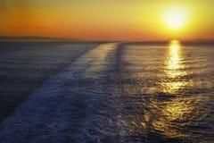 Kruisersleep in het overzees en de romantische zonsondergang Stock Afbeeldingen