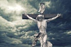 Kruisiging. Christelijk kruis met Jesus Christ-standbeeld over onweer Stock Foto