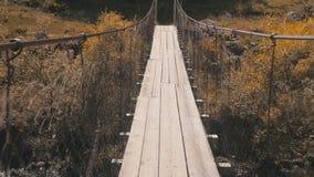 Kruising aan de overkant van een bergrivier door een opgeschorte houten brug De riviergang van de hangbrugberg stock video