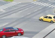 Kruising met Gele en Rode Auto Stock Foto's
