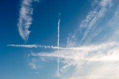 Kruispunten van sporen van vliegtuigen in de blauwe bewolkte hemel Royalty-vrije Stock Foto