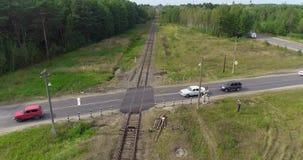 Kruispunten van weg en spoorweg, de kruising van spoor en weg Spoorweg op een mooi bosgebied stock video