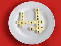 Kruiswoordraadselspel op schotel op lijst rode mat met woordensuiker, calorieën, diabetes en dieet die in de gezondheidsrisico va royalty-vrije stock afbeelding