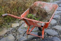 Kruiwagen in een tuin Stock Foto's