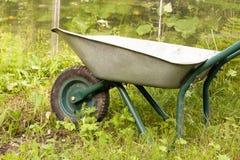 Kruiwagen in een tuin Stock Afbeelding