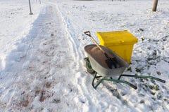 Kruiwagen met zand op de ijzige stoep stock foto's