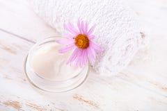 Kruka av att fukta framsidakräm och den härliga blomman på en vit träbakgrund naturlig organisk kosmetisk ansiktsbehandling royaltyfri bild