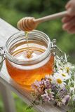 Kruka av Honey And Wooden Stick Are på en tabell utomhus arkivbilder