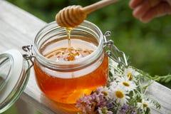 Kruka av Honey And Wooden Stick Are på en tabell utomhus arkivfoton