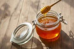 Kruka av Honey And Wooden Stick Are på en tabell utomhus royaltyfri foto