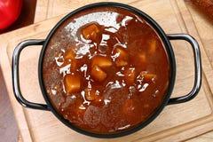 Kruka av nötkött- och potatissoppa på tabellen Royaltyfri Bild