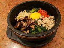 Kruka för sten för klassisk Bibimbap för Korea matgrönsak varm, rismorot, spenat, champinjon, gurka, havsväxt, rått äggulaägg och Arkivfoton