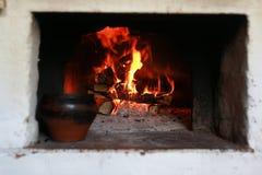 Kruka i ugnen med mat ugnsgaffeln Royaltyfria Bilder
