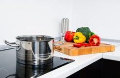 Kruka och grönsaker i modernt kök arkivfoto
