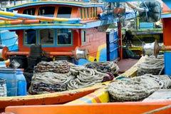 Krukken en gerolde kabels op kleurrijke die vissersboten naast elkaar worden vastgelegd stock foto's