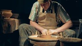 Krukmakerimannen skapar en bunke En person arbetar på en krukmakeri som gör en lera för att bowla på ett hjul lager videofilmer
