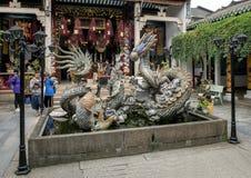 Krukmakeriskulptur av draken, karpen och sköldpaddan i en springbrunn i den Cantonese aulan i Hoi An arkivfoto