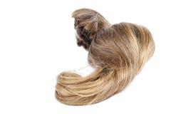 Krul van blond haar op een witte achtergrond stock afbeeldingen