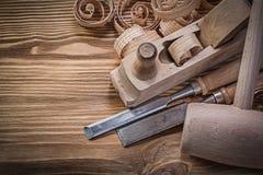 Krullade shavings för lägenhetstämjärn klumpa sig hyvlaren hammaren på det wood brädet Co Arkivfoton
