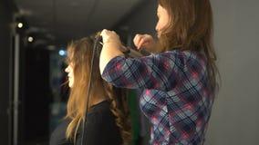 Krullande hår för frisör som bryner hårflickan i skönhetsalong steadicamskott lager videofilmer