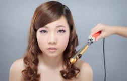 Krullande hår för härlig asiatisk kvinna Arkivbild