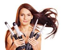 Krullande hår för kvinnaholdingjärn. Arkivbilder