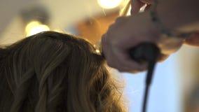 Krullande hår för stylist för ung kvinna stock video