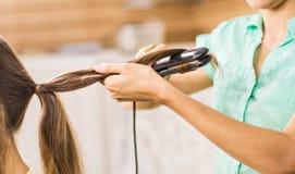 Krullande hår för stylist för ung kvinna Flickaomsorg om hennes frisyr Royaltyfri Foto