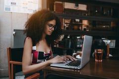 Krullend Braziliaans wijfje met netbook in straatkoffie met stock afbeeldingen