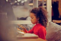 Krullend donker-haired meisjesgevoel betrokken bij het spelen van spel op tablet stock afbeelding
