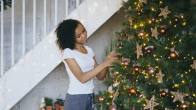 Krullend gemengd rasmeisje die Kerstboom verfraaien die thuis voor Kerstmisviering voorbereidingen treffen royalty-vrije stock foto