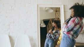 Krullend grappig Afrikaans Amerikaans meisje die en met droogkap voor spiegel thuis dansen zingen stock videobeelden
