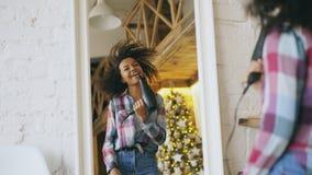 Krullend grappig Afrikaans Amerikaans meisje die en met droogkap voor spiegel thuis dansen zingen royalty-vrije stock fotografie