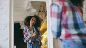 Krullend grappig Afrikaans Amerikaans meisje die en met droogkap voor spiegel thuis dansen zingen stock afbeeldingen