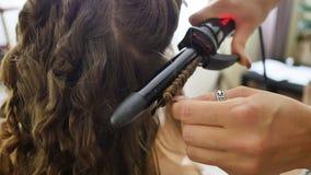 Krullend haar in schoonheidssalon Professionele kapper die krullend ijzer voor haarkrullen gebruiken bij salon stock video