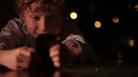 Krullend haar weinig jongen die met smartphone met de achtergrond van Kerstboomlichten spelen stock footage