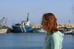 Krullend haarmeisje bij de kust stock foto
