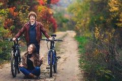 Krullend-haired mustachioed kerel en een erts-haired meisje in de herfsttribune met fietsen op weg en tonen vrolijke emoties royalty-vrije stock afbeelding