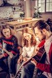 Krullend meisje die het blije luisteren voelen aan haar vriend die de gitaar spelen stock foto