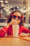 Krullend meisje die kleurrijke toebehoren dragen die milkshake drinken royalty-vrije stock foto