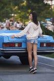 Krullend meisje en blauwe cabriolet Stock Afbeelding