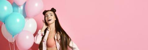 Krullend meisje in jasje die kleurrijke ballons voor partij houden en met verraste gezichtsuitdrukking stellen stock afbeelding