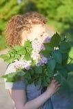 Krullend meisje met een boeket van sering op aard op een de zomerdag royalty-vrije stock afbeelding