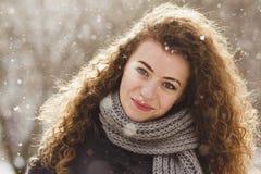 Krullend meisje op de achtergrond van sneeuw Royalty-vrije Stock Fotografie