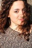 Krullend, mooi jong meisje met lichte glimlach Royalty-vrije Stock Foto's