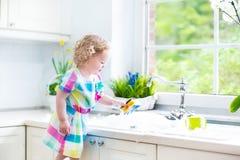Krullend peutermeisje in de kleurrijke schotels van de kledingswas Stock Afbeelding