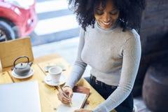 Krullende Afrikaans-Amerikaan in een grijze jasjevergadering in moderne koffiezitting dichtbij venster Stock Foto's