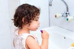 Krullende Babypeuters die tanden borstelen Jong geitje gezond concept De Tandhygi?ne van het kind royalty-vrije stock fotografie
